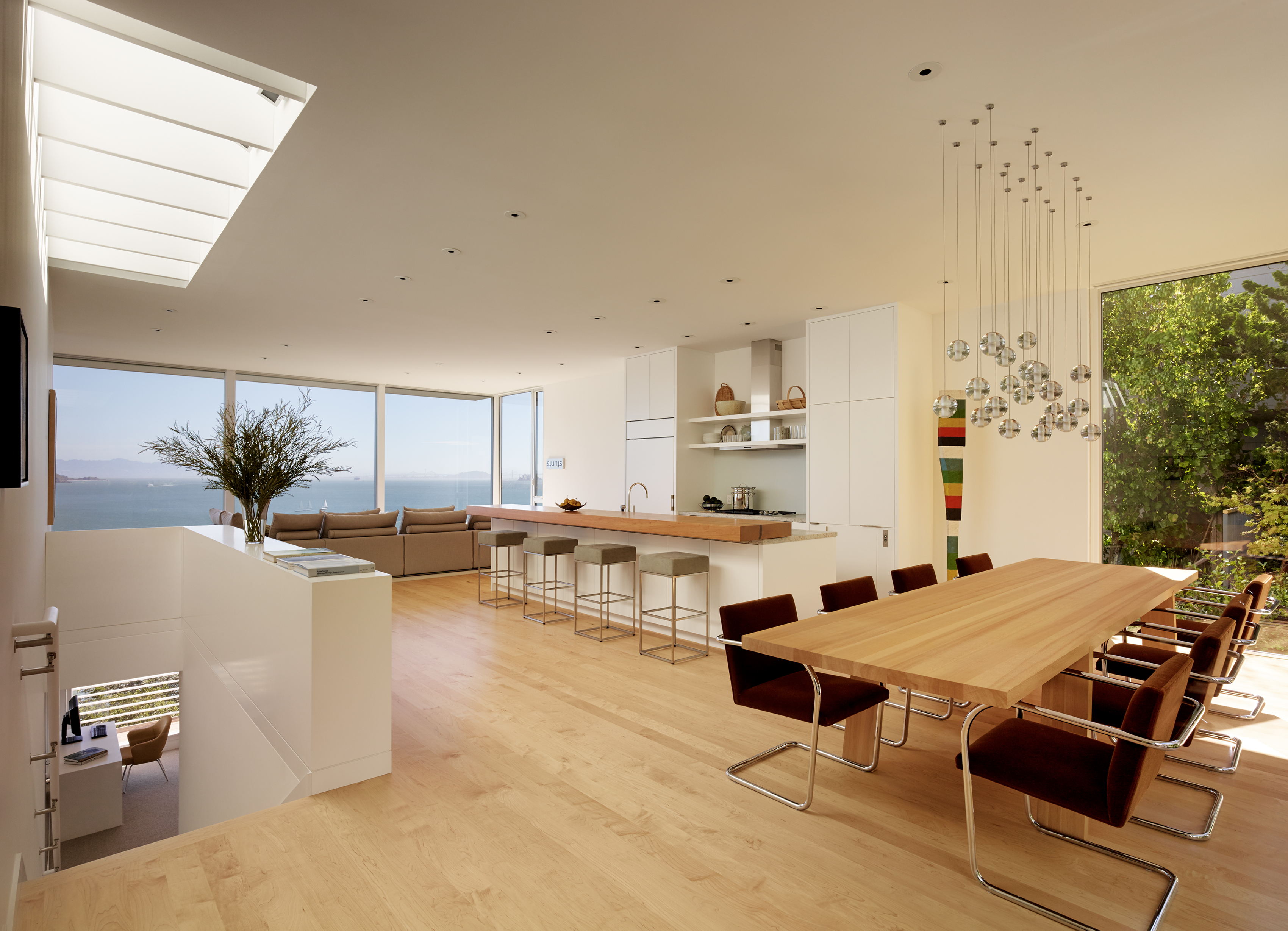 The staircase opens up into the dining room, kitchen, and living room. The open concept really allows visitors to move from the lush backyard to viewing the bay. The light natural wood floors are mirrored in the dining room and in the top of the eat-in bar at the kitchen island. Above the dining table is a unique light fixture.