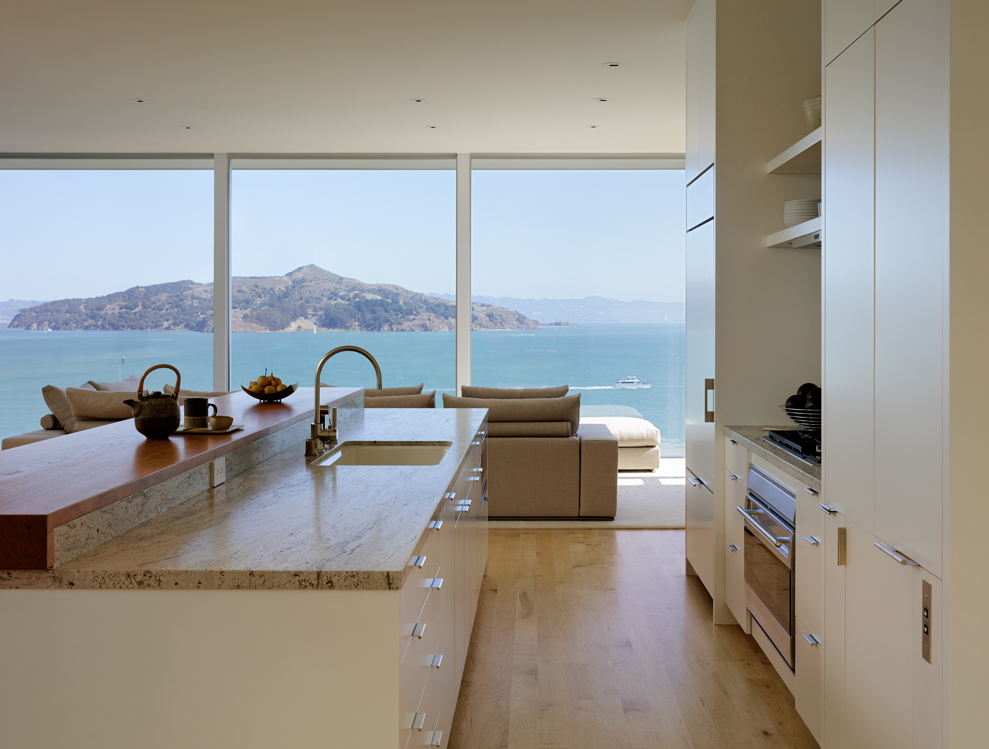 The white cabinets of the kitchen have chrome handles that complement the stainless steel appliances and other fixtures. The two-tier kitchen island is granite and wood. A beautiful view of Angel Island is prominent while working in the kitchen.
