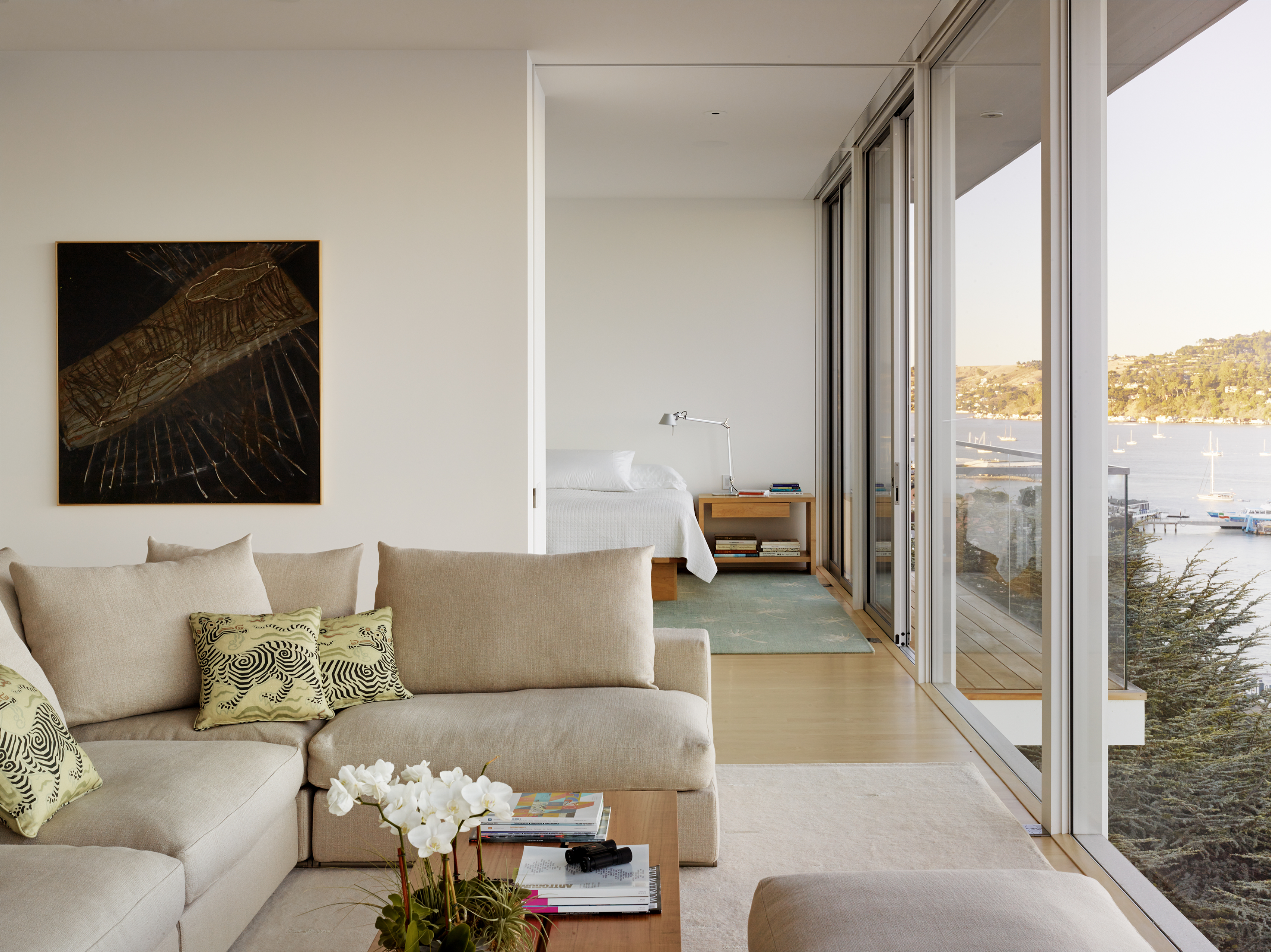 From the library, the living room is just a short few steps down the hallway. The plush sectional looks directly out of the floor-to-ceiling windows towards the bay, with no other distracting focal points, like a television.