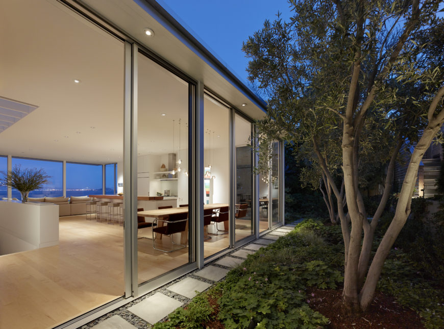 Even from all the way in the back garden, you can see through the home to the bay. Recessed lighting under the eaves provide lighting for the backyard path.