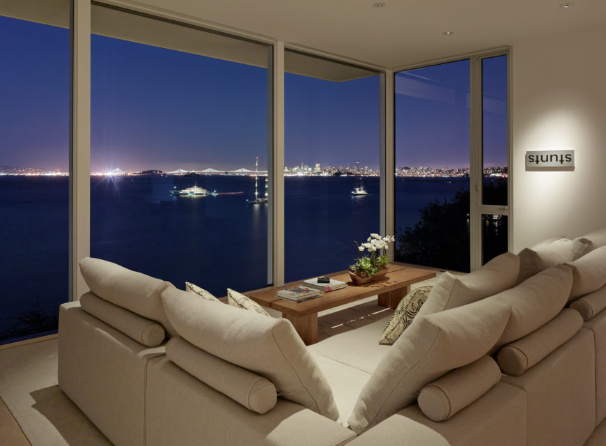 The view across the bay at nighttime is breathtaking. A simple wooden coffee table rests on the cream rug that covers the natural wood floor.