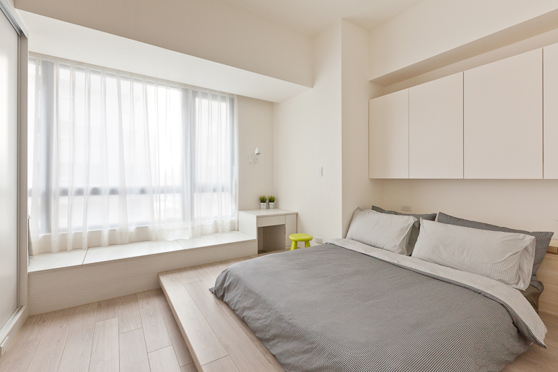 The bedroom holds a lighter touch, with white walls surrounding the hardwood flooring. Bed sits on a raised platform in abundant sunlight through the large window.
