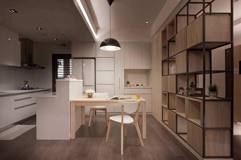 The kitchen is defined by a large cubical wall at right, with wood cubbies set in a metal framework. The two-tiered island is paired with a light wood dining table as the centerpiece, with off-white cabinetry surrounding.