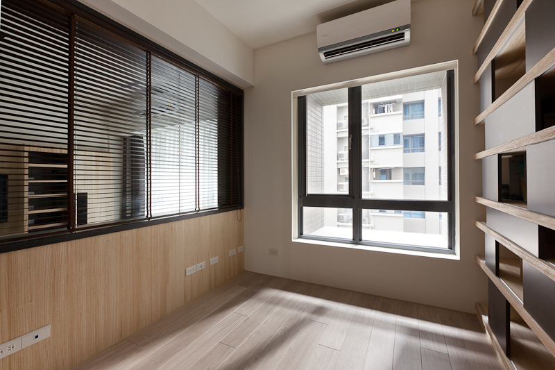 Moving inside the window-wrapped office room, we see a large exterior window and array of built-in shelving to the right.