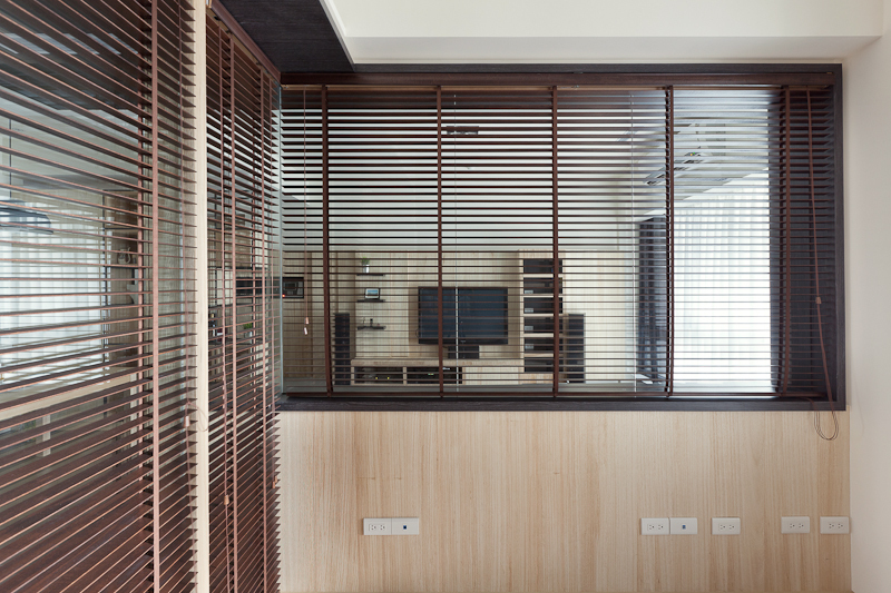 Brown hued shades grant the office space privacy. When opened, they allow the visual space to extend to the surrounding rooms.
