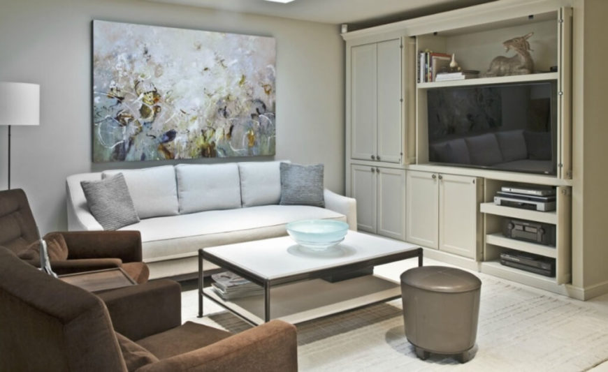 This cozy family room sits connected to the kitchen, on a lowered tier, with a mixture of brown and white thick-cushioned seating and a white topped, metal frame coffee table at center. Entertainment cabinetry matches the soft beige hue of the kitchen.