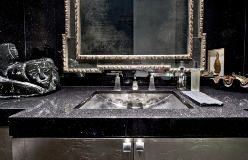 This bathroom appears in dark contrast to the dominant white hues of the home, with granite countertop on this stainless steel vanity.