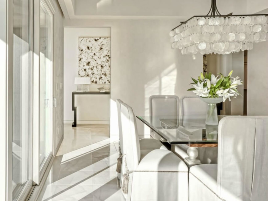 The dining room stands in bright white tones, with an attention grabbing scale-filled chandelier over the glass top dining table. Marble tile flooring continues the elegant look from the entry hall.