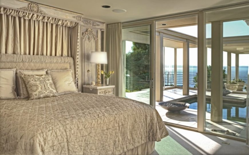This bedroom is filled with rich, traditional carved wood detail flanking the bed. Sliding glass in this space opens directly to the pool equipped courtyard, with views of the Puget Sound afforded.