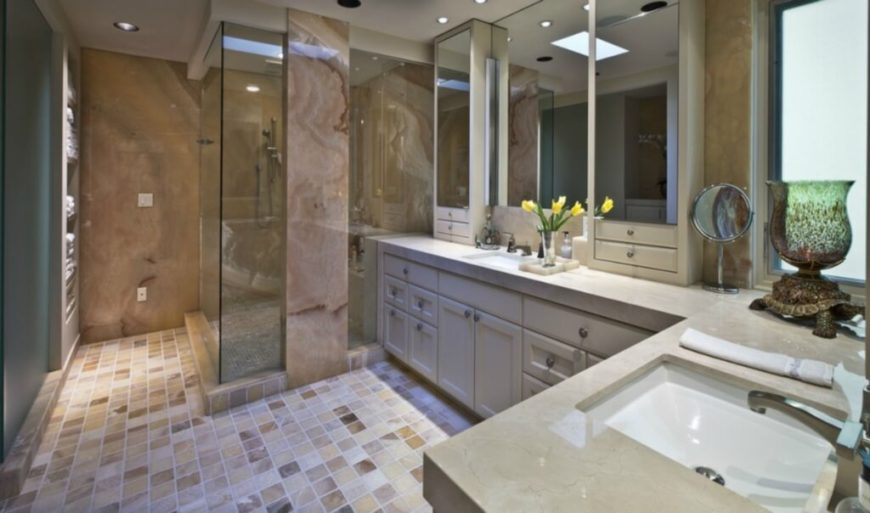 The large master bath is filled with tonal variety, with multicolored tile flooring, beige countertops, and a glass enclosed shower supported by a massive marble column.
