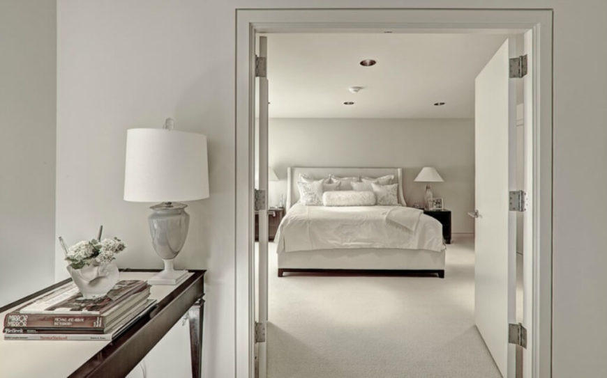 Another bedroom, appearing in swaths of white, features a double door opening with dark carved wood side table at left.