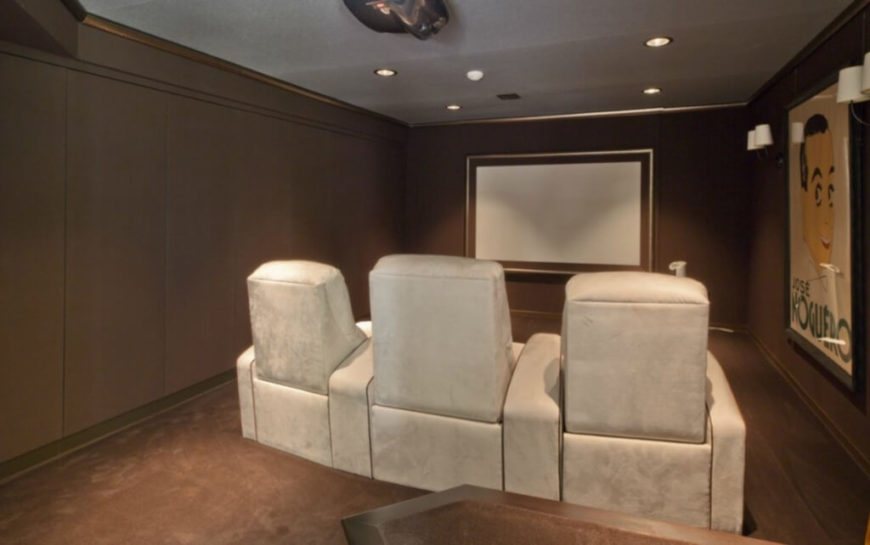 The home features a cozy yet full fledged media room, with theater style seating and overhead projector for movie viewing.