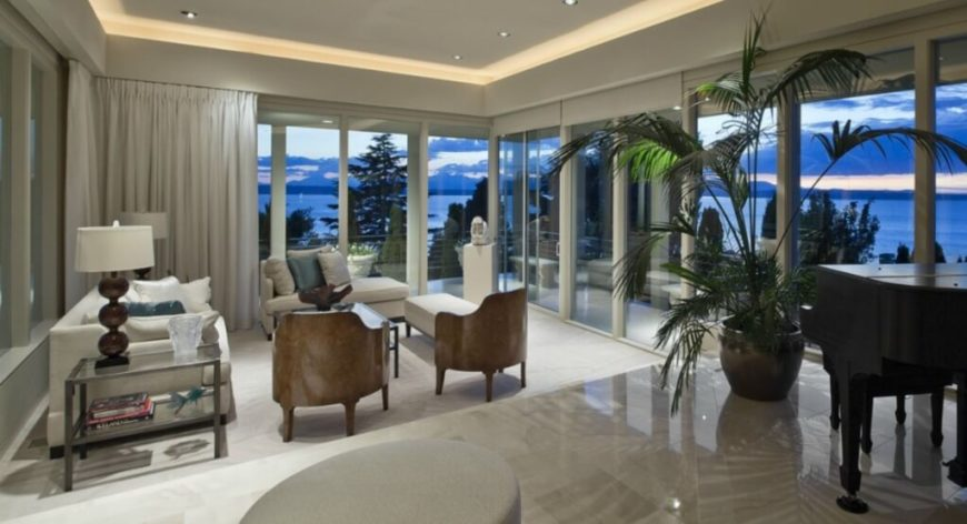 The living room stands upon white carpet, a few steps lower than the marble flooring of the rest of the home. Full height glass panels wrap the entire space, affording massive vistas over the water.