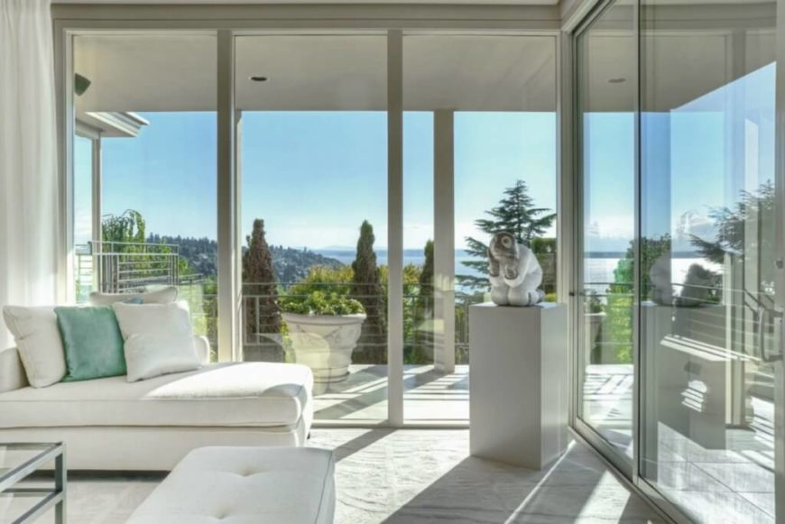 White sofa and ottoman stand with a statue in the living room corner, sunlit through the full height glass. The wraparound balcony blends seamlessly with this interior.