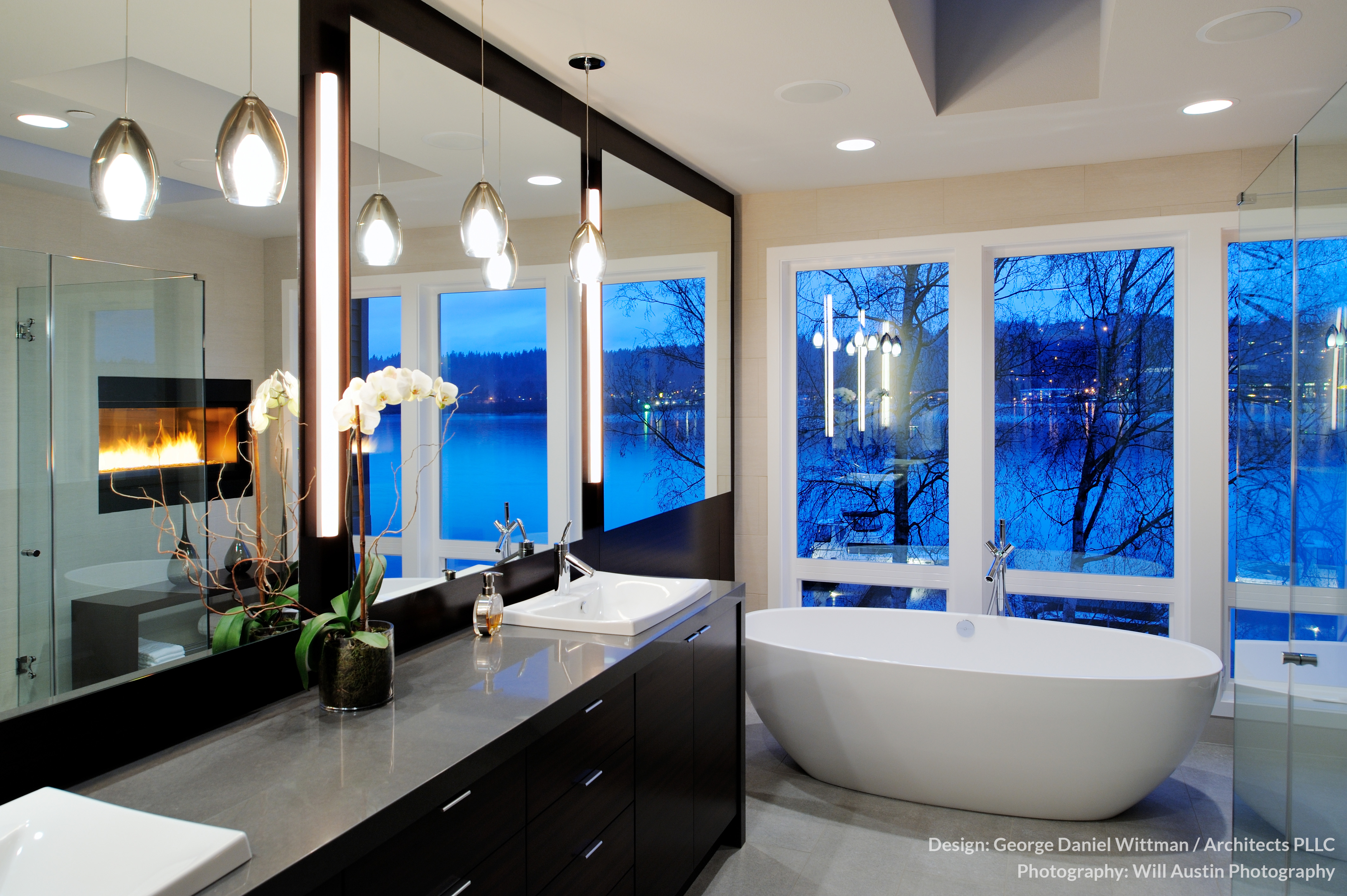The master bath houses a large pedestal tub with expansive views over the water via full height windows. All-glass shower enclosure can be seen at right.