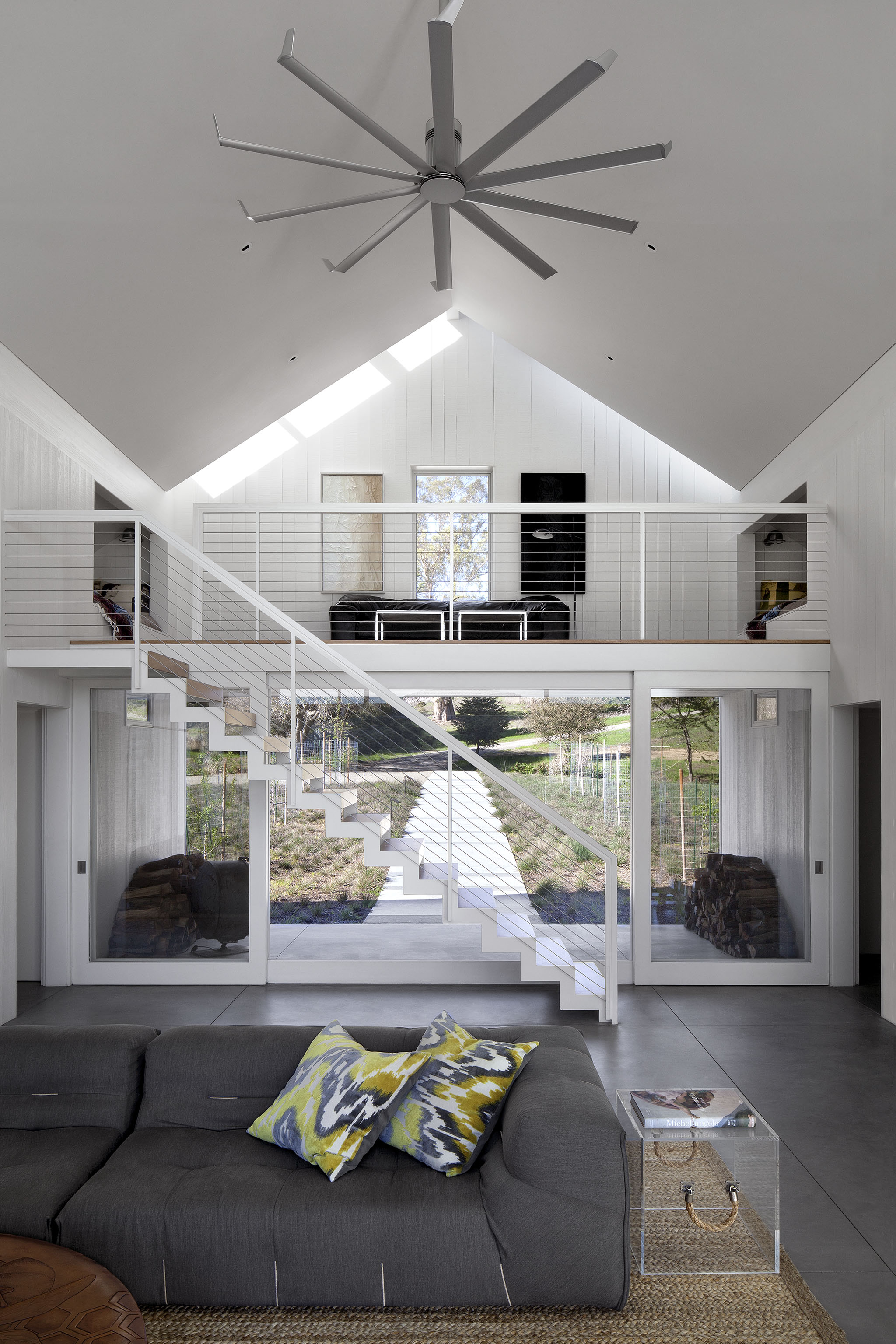 The two-story living room also holds this loft area above the doorway, with subtle skylights framed against the roof edge. A massive aluminum ceiling fan efficiently circulates air in the large space.