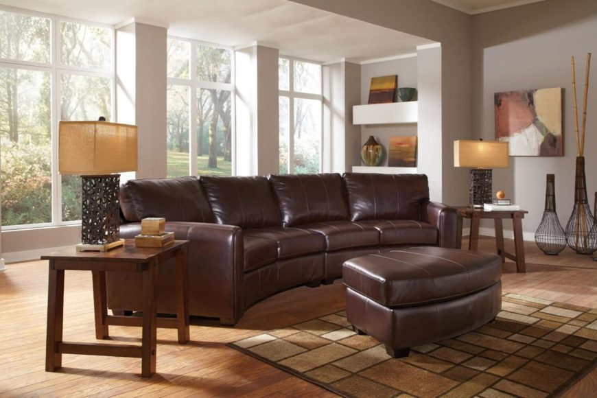 This traditionally styled curved sectional features thick cushioned brown leather seating with a matching ottoman, over hardwood construction and feet.
