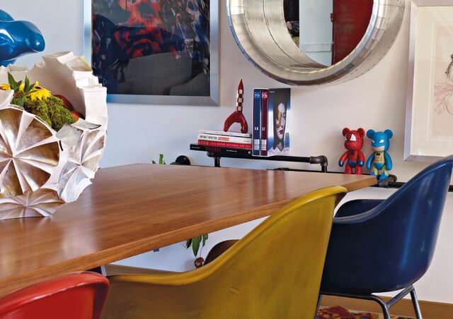To the right of the table is an industrial-style shelf used to hold books and a pair of superhero teddy bears. The wall itself has multiple works of art and a mirror.