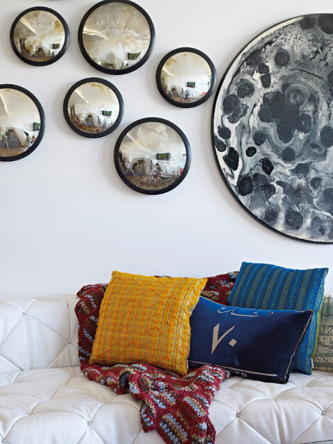 The wall behind the sofa has arrangement of hubcaps and a large circular piece of art repurposed into a wall display. Brightly colored, patterned, and textured accent pillows brighten up the white sofa.