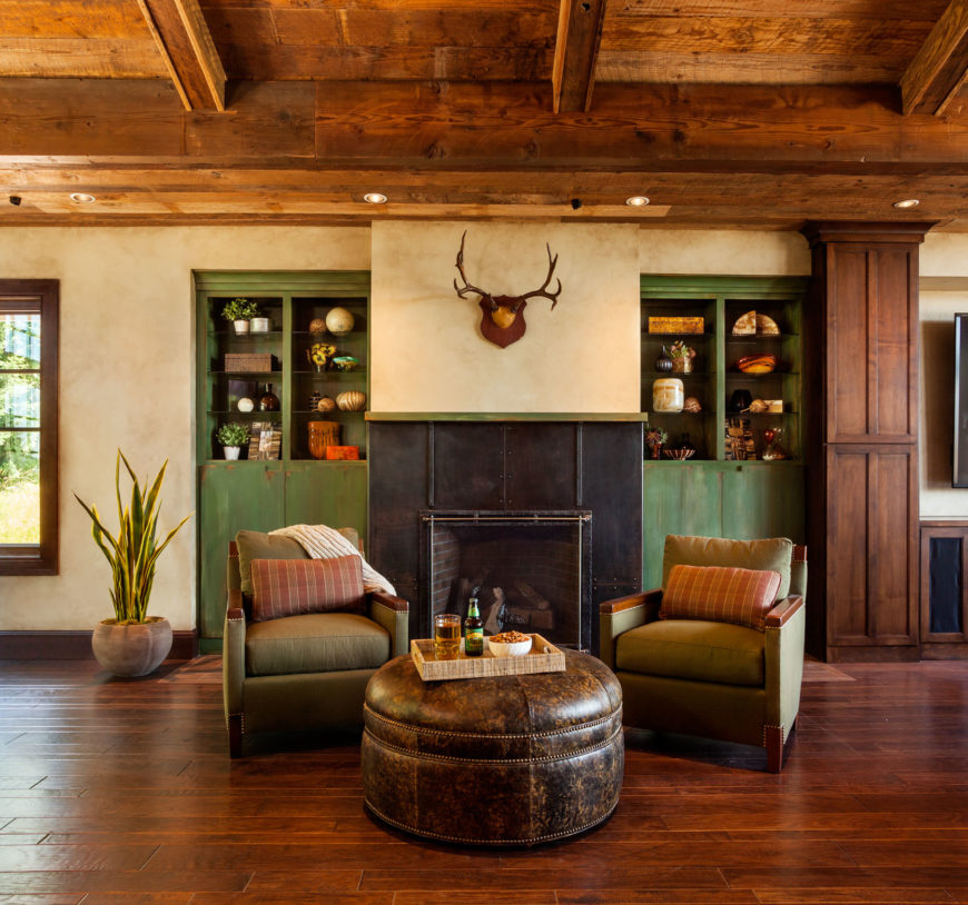 Adjacent to the built-in entertainment center centered in front of the leather sectional is a small open-hearth fireplace in iron. A distressed leather ottoman serves as a coffee table with a small wicker tray.