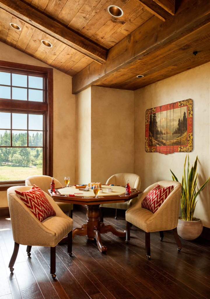 In the corner by the window is a card table with ornate legs and built-in cup holders. Plush rolling chairs surround the table.
