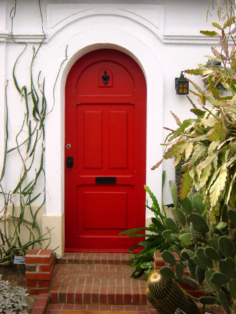 The entry to this home is an arched door decorated with a black, metallic handle, mailbox slot and knocker. The steps leading up to the door are made of bricks and lined with various species of cacti, each with a placard.