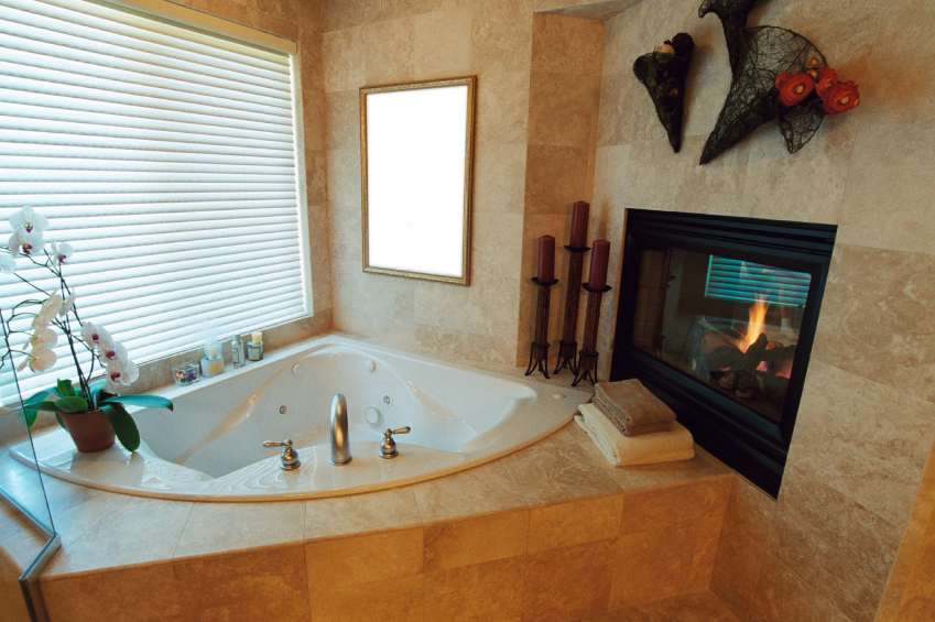 This Tile Clad Bathroom Features A Cozy Corner Soaking Tub And Wall Mounted  Fireplace,