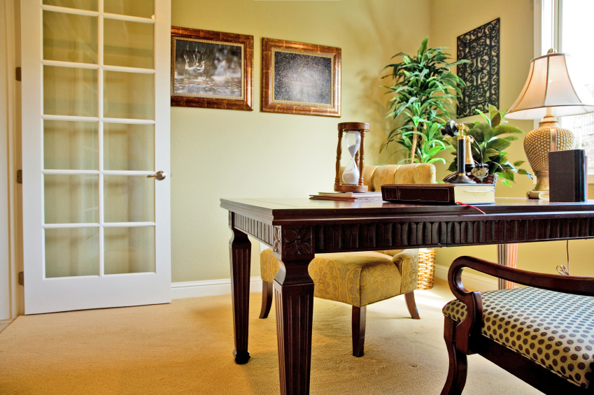 Here we have a cozy, traditionally appointed home office, with ornate writing desk and a pair of accent chairs: one in wood frame with polka dot seat cushion, the other upholstered in button tufted fabric. Soft hued walls stand over beige carpet with white molding for an inviting look.