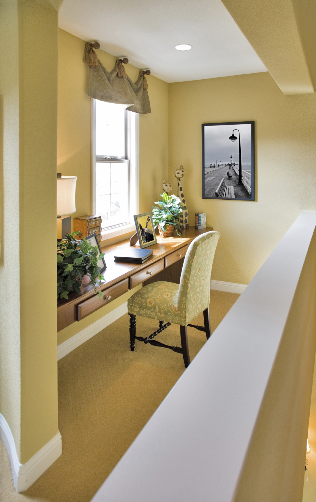 The soft yellow hues of this study brighten and make the cozy space feel larger, with a slim writing desk in dark wood standing below a single white framed window. The room stands on a loft space, with low wall defining the edge.
