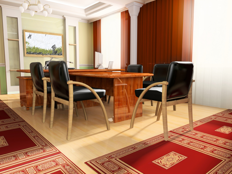 This large, brightly toned office features a mixture of traditional and contemporary elements, with a sleek natural wood, multi-section desk at center. Ornate red rugs surround the furniture, over light hardwood flooring.