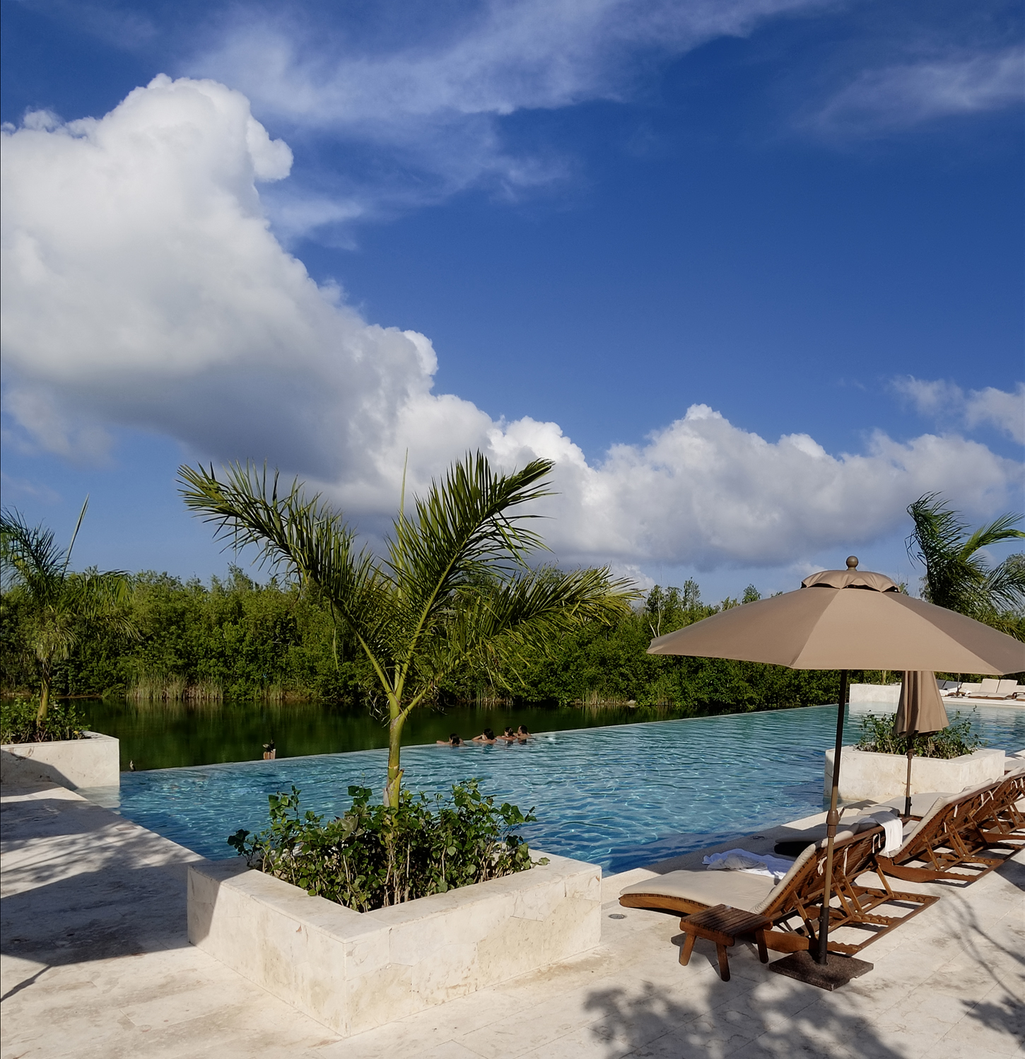 This Gorgeous Resort Pool Has Umbrella Shaded Lounge Chairs Near The Steps  Leading Into The