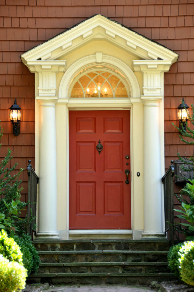 The red of this door is a more muted shade of brick-red, which is still a shade or two brighter than the shingle siding. The series of four steps leading up to the door are stone and mortar. The short walkway up to the steps is lined in easy-to-care-for shrubs.