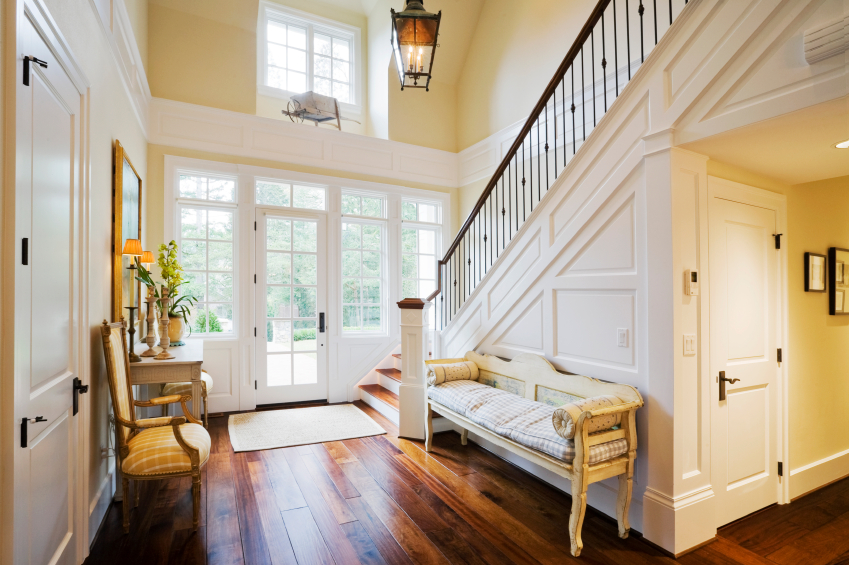 Contemporary entrance hall design with hardwood floor and white staircase