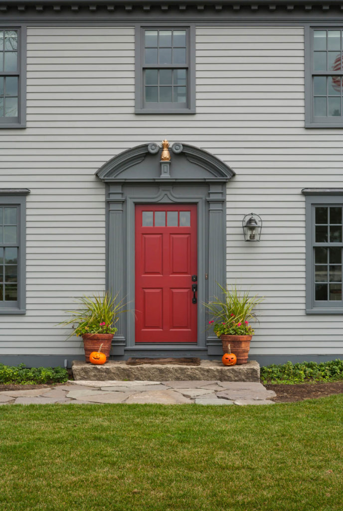 The manicured front lawn has a flagstone path leading up to the front door, which is decorated festively for Halloween. The dusky blue of the siding and trim is emboldened by the pop of the red door. The trim is ornately carved and a golden accent at the top-center adds additional elegance.