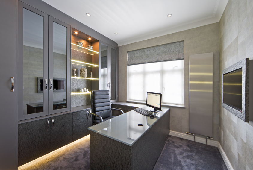 This home office features a distinctly ultra-modern look, with stainless steel, glass, and dark grey textures filling the space. Wall mounted glass shelving features inner lighting as well as light spilling from beneath.