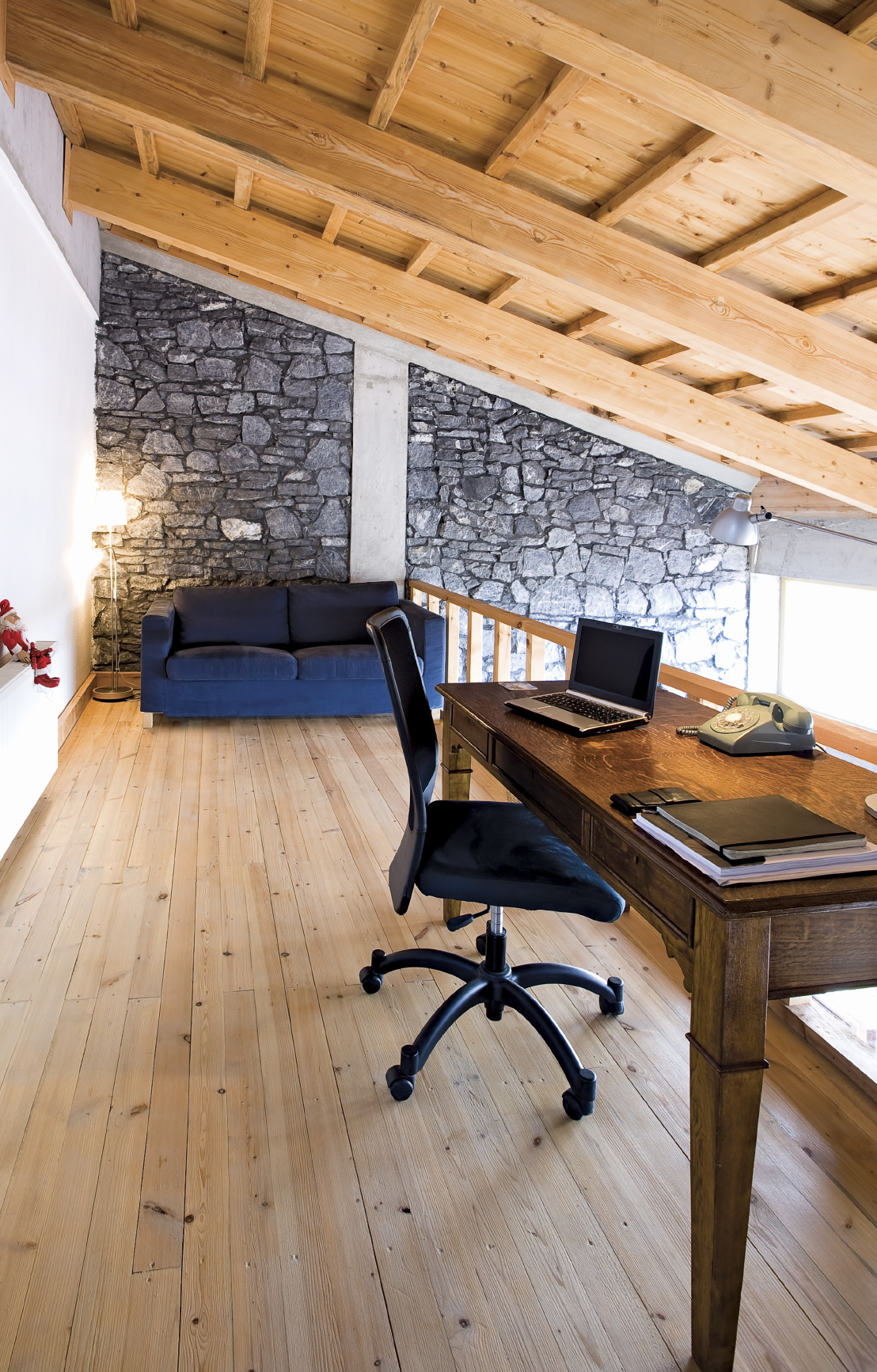 Occupying a natural wood loft in a rustic styled home, this office holds a traditional wood writing desk and bold blue sofa next to an immense stone wall.