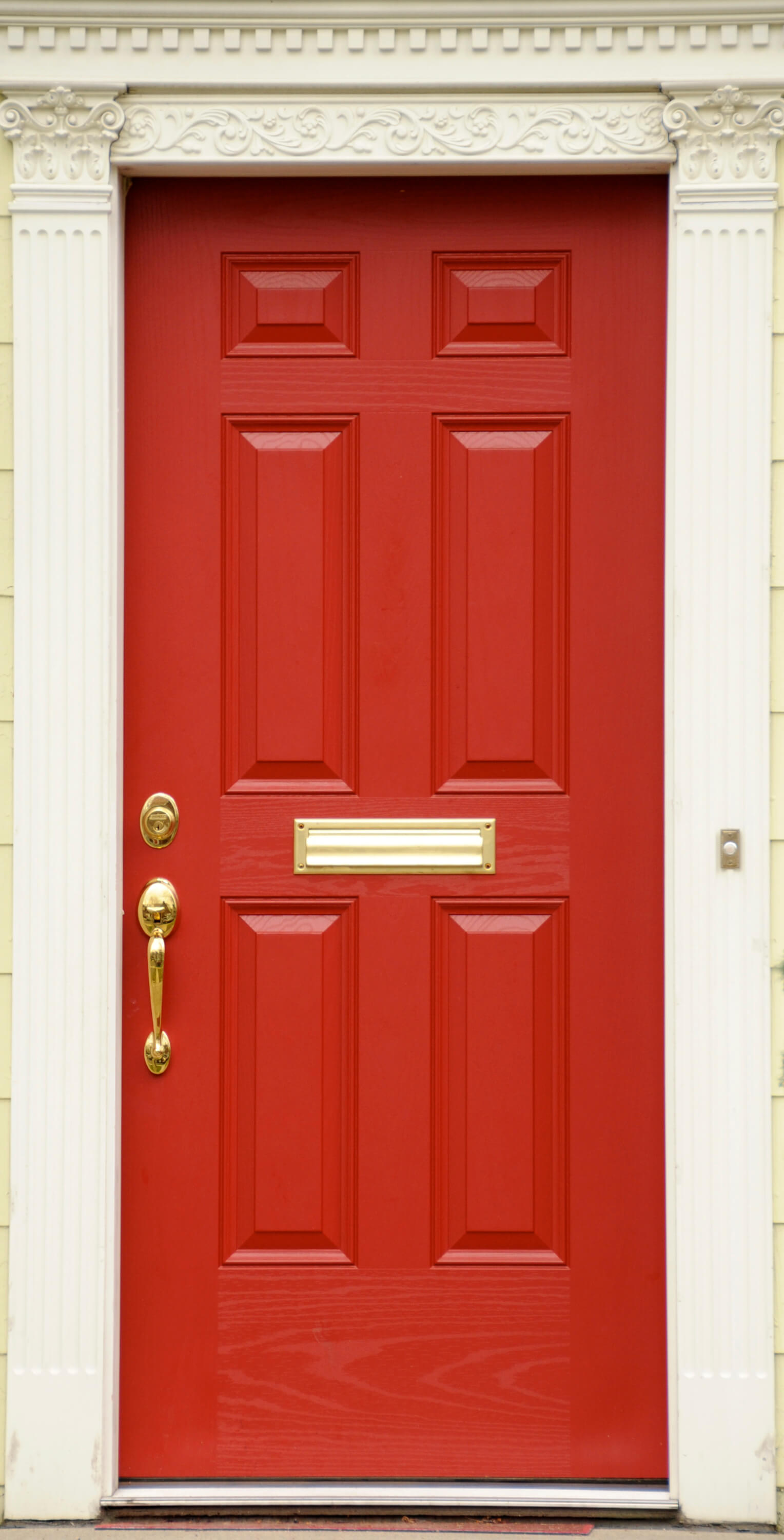 The wood grain of this painted door is still clearly visible beneath the bold red. The ornate trim adds elegance to the otherwise unassuming, modestly-sized porch. The fixtures on the door are all brand new, in a shiny gold finish.