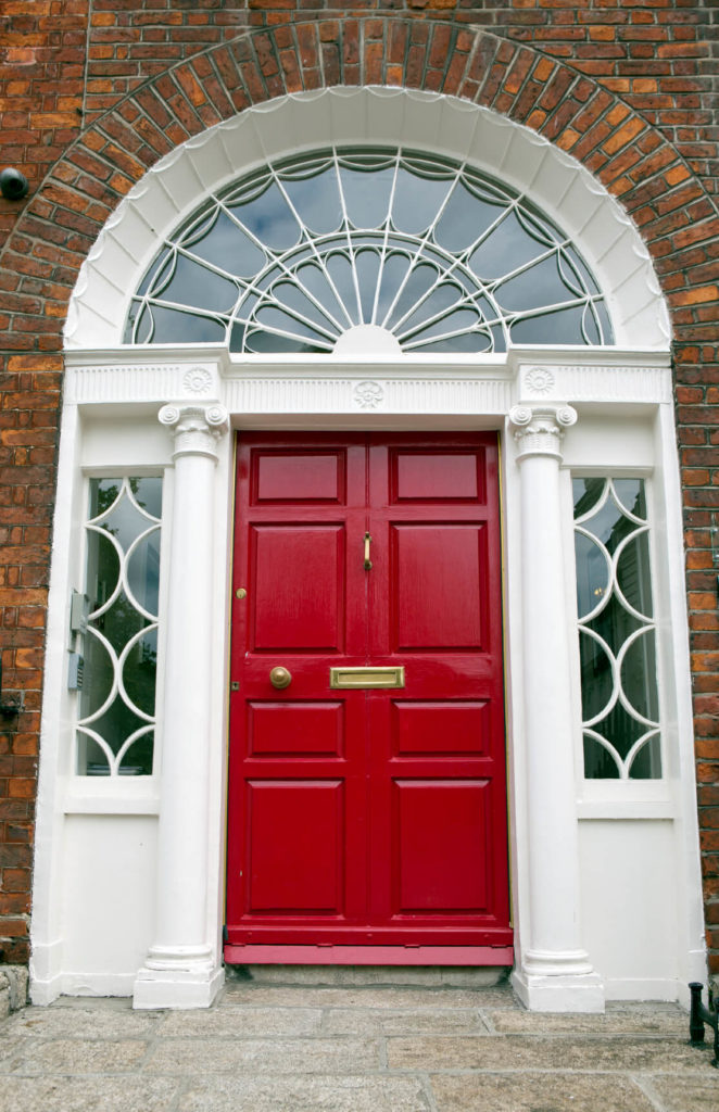 The arched frame surrounding the bold red front door is in a pristine white with sidelights and an arched transom. The brick facade of the building arches up around the transom.