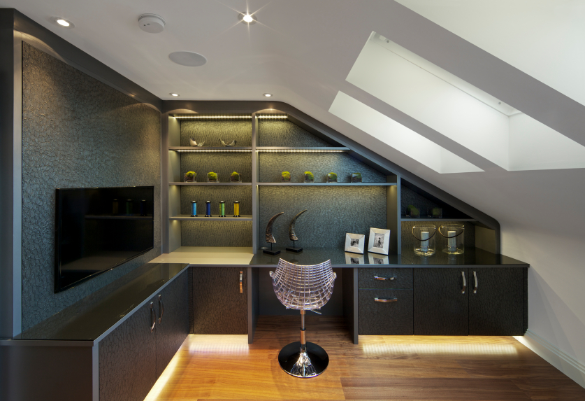 In this sloped-ceiling space, we see the high contrast between charcoal toned shelving and wraparound desk, and the white walls and bright, natural hardwood flooring. Inner-lit shelving and under-cabinet lighting provide a sparkling edge and keep the dark material warmly lit. A singular chrome mesh chair stands apart.