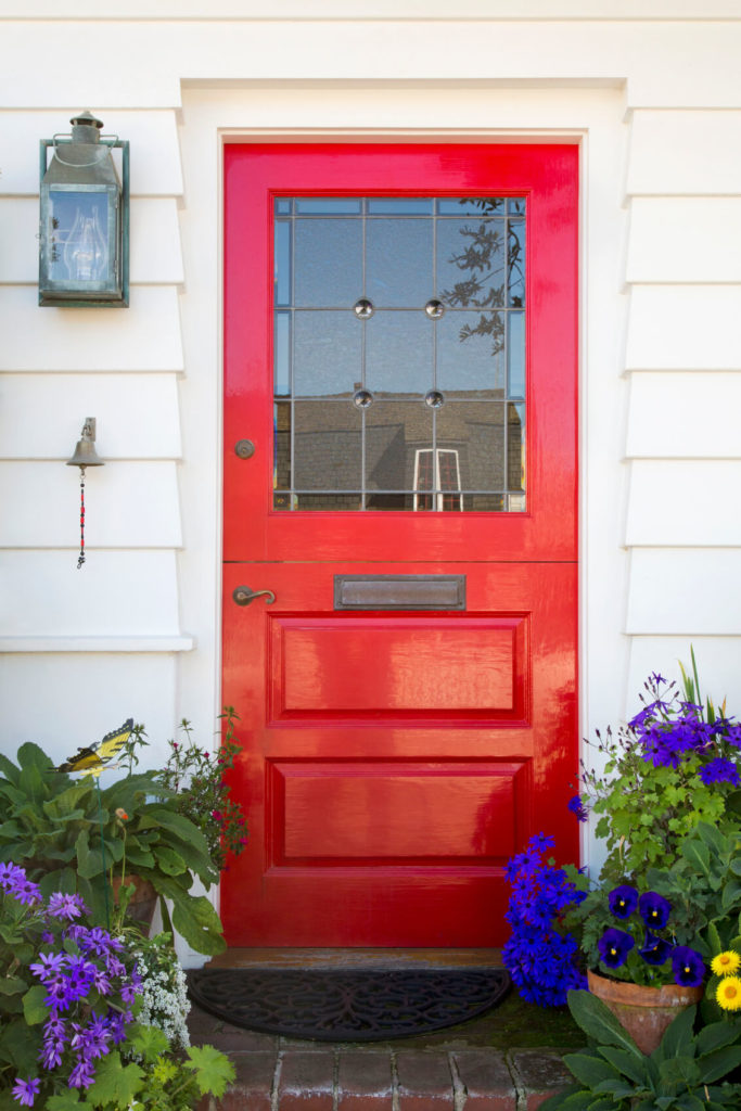 The small stoop of this home is full of beautiful, vibrant potted flowers, including pansies and gerbera. The decorative glass panels on the upper half of the door obscure the view of the home from the outside while still letting in some natural light.