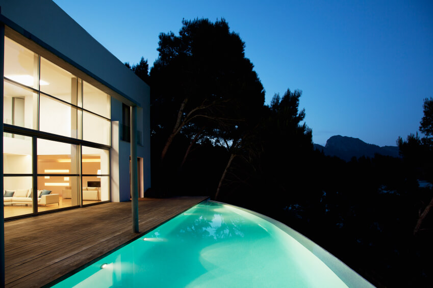 The curved infinity pool extends from the wooden patio and has small lights lining the straight edge.