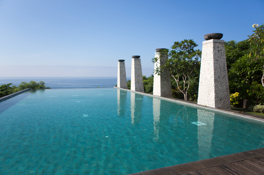 This wide pool has monolithic stone pillars with bowls at the top lining one side. The bowls can be lit at night for an amazing visual effect.