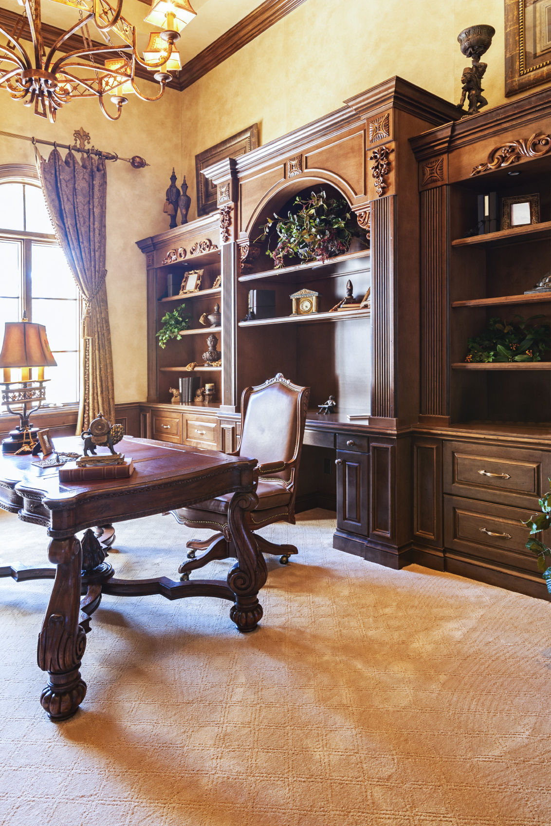 This home office is a truly ornate, traditional affair, with carved wood, leather topped desk standing at center below a massive, wall sized rich wood shelving set. Chandelier, array of art pieces, and even etched carpeting add detail.