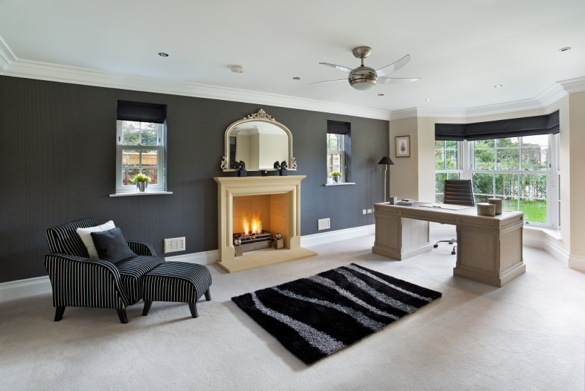 In this sprawling, white carpeted study, a fireplace commands attention at the center of a dark toned wall, between a striped lounge armchair and immense natural wood desk. A large bay window invites natural light, along with a pair of smaller windows flanking the fireplace and overhead mirror.