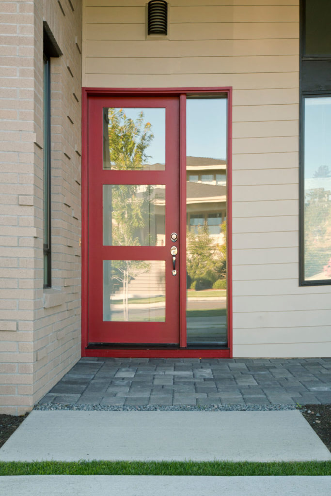 This more modern example has a single sidelight on the right side of the door, which has three glass panels taking up the majority of the door. The facade of this home is partially a dusky, beige brick or a light beige siding.