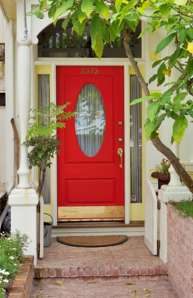 The aged brick walkway up to the front door of this home has a small white gate that adds cottage charm to the bright red door with gold finished accents.