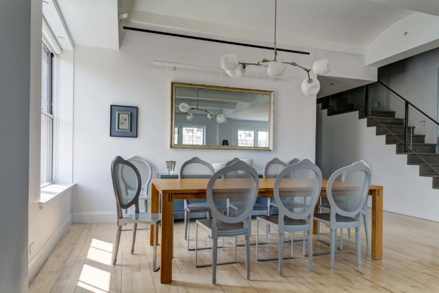 A dining area with a rectangular wood table surrounded by gray round back dining chairs. It is decorated with a wall mirror mounted above the buffet table and a modern chandelier.