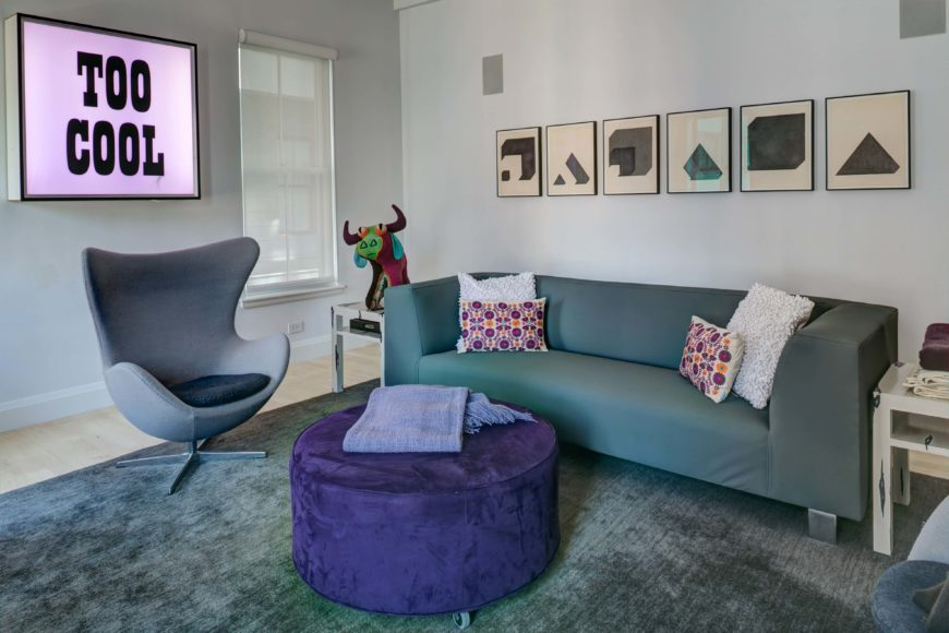 The living room itself centers an array of modern furniture over a soft grey rug, defining the area within the larger open space. Minimalist sofa and shell-design chair flank a large purple circular ottoman, beneath striking art pieces on the walls.