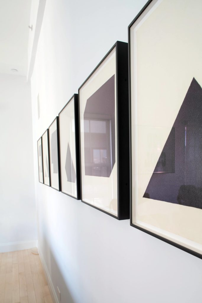 The series of minimalist pieces on the living room wall are framed in dark wood, adding detail and contrast to the white space.