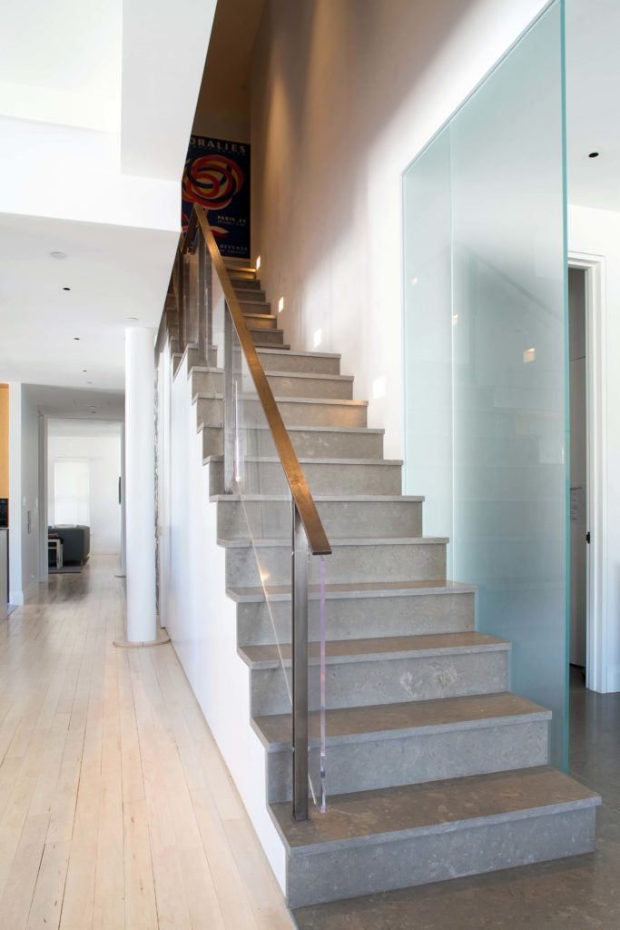 Finally we return to the central open space and the stone staircase, with metal and glass railing. The light hardwood flooring reaches throughout the home brightening with the white walls all around.